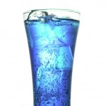 Glass of blue carbonated drink with ice